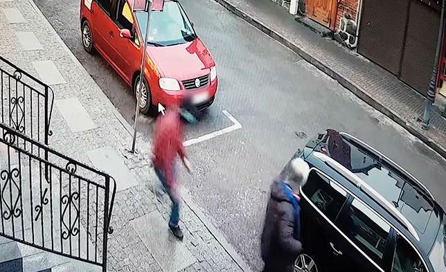 Napastnik (w czerwonej kurtce) atakuje wychodzącego z kantoru przedsiębiorcę
