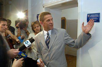 Długosz pokazuje tabliczkę, którą - jak powiedział dziennikarzom, będzie musiał zdjąć