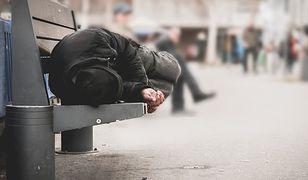 Osoba bezdomna śpi na ławce w wielkim mieście