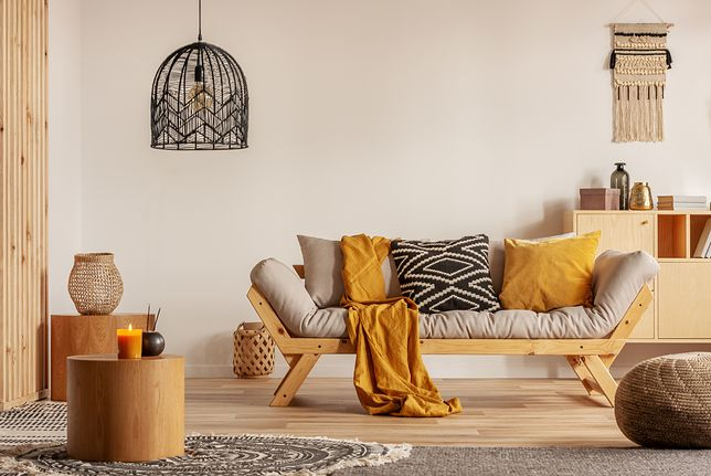 Scandinavian sofa with pillows and dark yellow blanket in bright living room interior with black chandelier