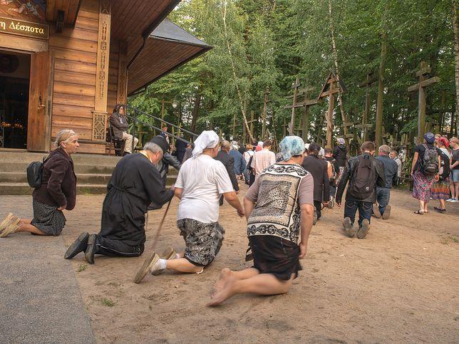 Pielgrzymi okrążają na klęczkach cerkiew, stojącą na Grabarce