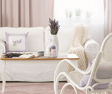 Wooden coffee table with pastel candles, fresh lavender and open book in real photo of bright sitting room interior with white couch