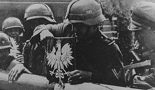 Niemieccy żołnierze zrywają polskie godło ze szlabanu granicznego, 1 września 1939 r.