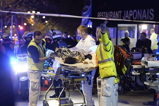 Ratownicy udzielają pomocy rannemu w zamachu w Paryżu w listopadzie 2015 r.