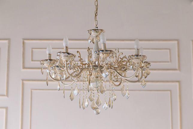 Aranżacja salonu w stylu glamour nabiera właściwego sobie blichtru dzięki oświetleniu z kryształami