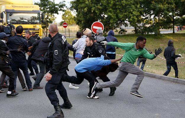 Imigranci uciekają przed francuską policją, by dostać się do pociągu jadącego do Wielkiej Brytanii - Calais, 30 lipca