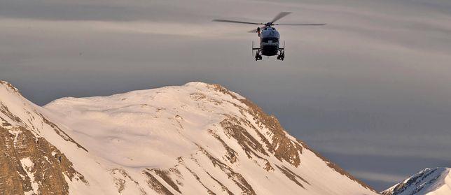 Helikopter przelatuje nad szczytami Alp