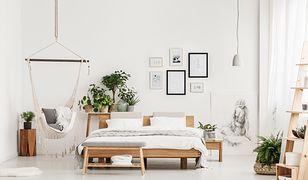 Sypialnia w stylu skandynawskim nie musi być surowym wnętrzem. Ocieplać je mogą dodatki w formie zielonych roślin oraz drewniane meble.