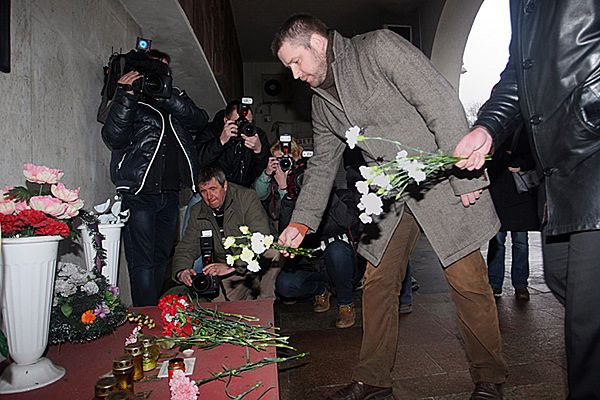 Kwiaty i znicze pod tablicą przy wejściu do stacji metra