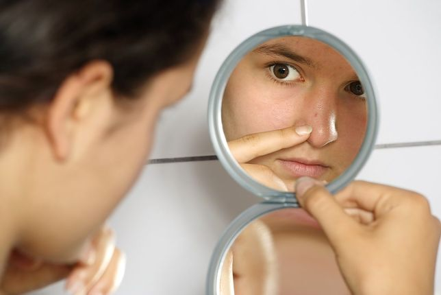 Young teenage female holding a mirror looking at her pimple with concern.