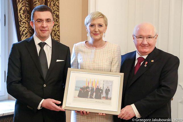 Marek Małecki (po prawej) odbiera od Agaty Dudy i fotografa Jacka Łabędzkiego (po lewej) wylicytowaną przez siebie fotografię Pierwszej Damy.