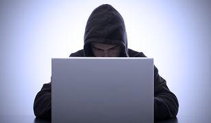 Groźny facet w kapturze pracujący na komputerze.