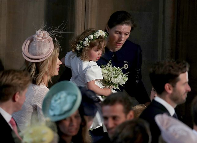 WINDSOR, UNITED KINGDOM - MAY 19: A crying flower girl is comforted inside the entrance to the chapel before the wedding of Prince Harry to Meghan Markle in St George's Chapel at Windsor Castle on May 19, 2018 in Windsor, England. (Photo by Owen Humphreys - WPA Pool/Getty Images)