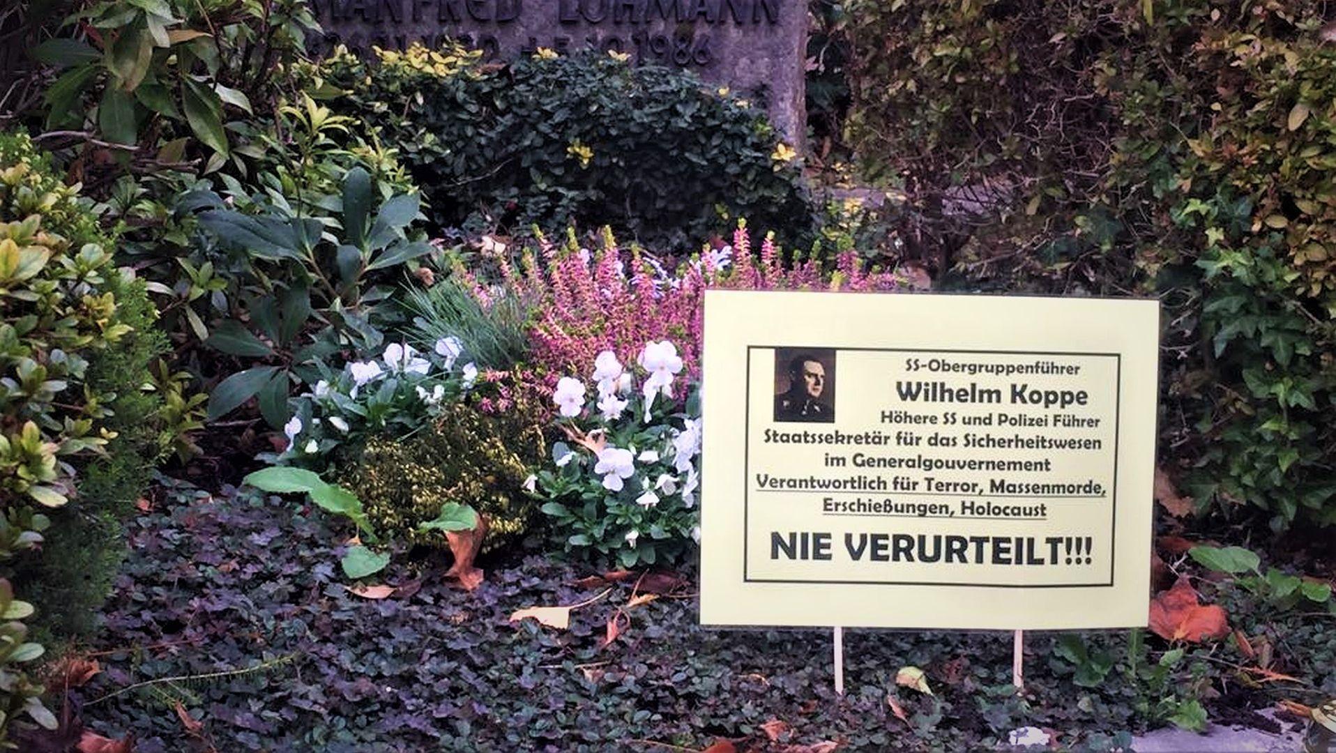 Grób Wilhelma Koppe z podłożoną tabliczką z informacją o tym, że nie został ukarany za swoje zbrodnie