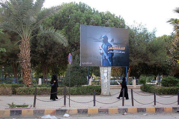 Kobiety w stolicy samozwańczego kalifatu obok propagandowego plakatu; 2014 r.