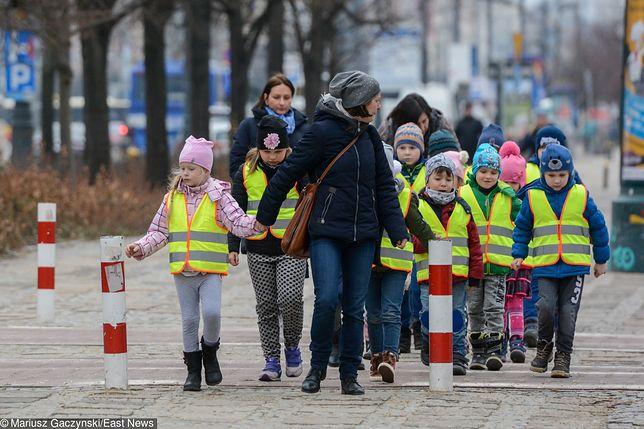 Dzieci w kamizelkach odblaskowych.