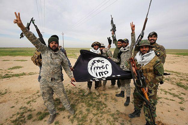Bojownicy pozujący z flagą ISIS