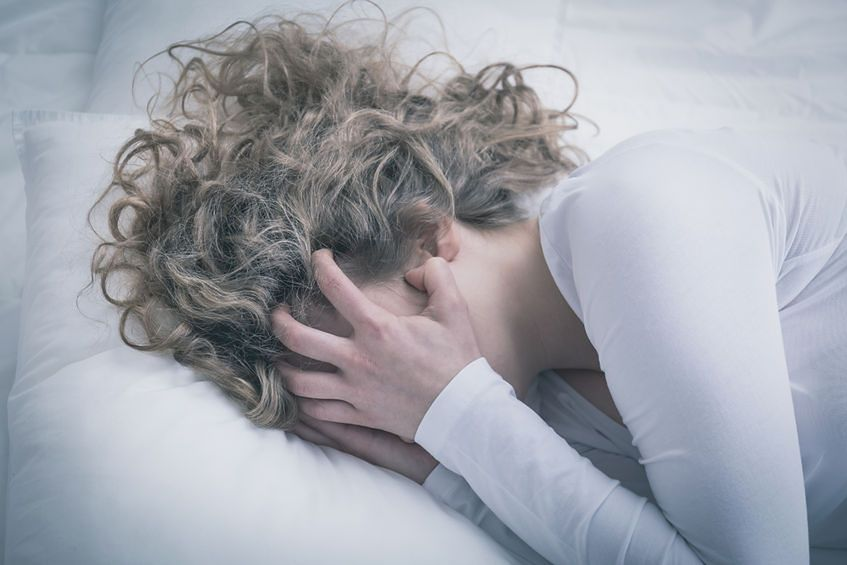 Zrozpaczona kobieta obejmująca twarz