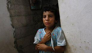 Dziecko płacze po izraelskich nalotach, w których zginął 22-letni mężczyzna
