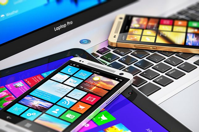 Mobility and modern internet business communication technology concept: macro view of office laptop or notebook, tablet computer PC and black glossy touchscreen smartphones with color interfaces with icons and buttons