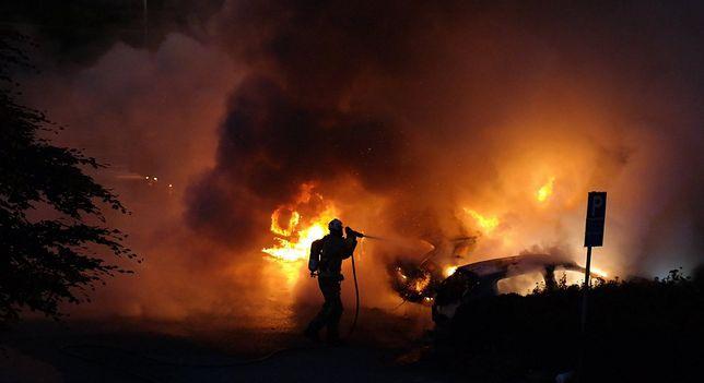 Strażak gasi płonące samochody