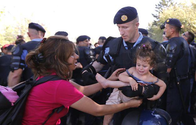 Chorwacki policjant zabiera dziecko uchodźczyni do obozu dla uchodźców nieopodal miasta Tovarnik