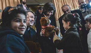 Minister Joanna Wronecka z księdzem Tomaszem Jegierskim wręczają prezenty dzieciom
