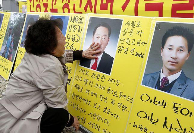 Matka nauczyciela, który zginął w katastrofie, przed portretem syna