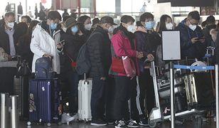 Kolejka na lotnisku. Pasażerowie noszą specjalne maski.