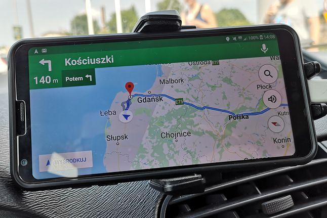 """Smartfon w uchwycie na szybę lub (w tym przypadku) mocowanym do deski rozdzielczej to dziś dużo częstszy widok od """"klasycznych"""" nawigacji."""