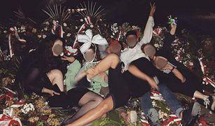 Grupa młodych ludzi sfotografowała się na wieńcach pod pomnikiem rotmistrza Pileckiego.