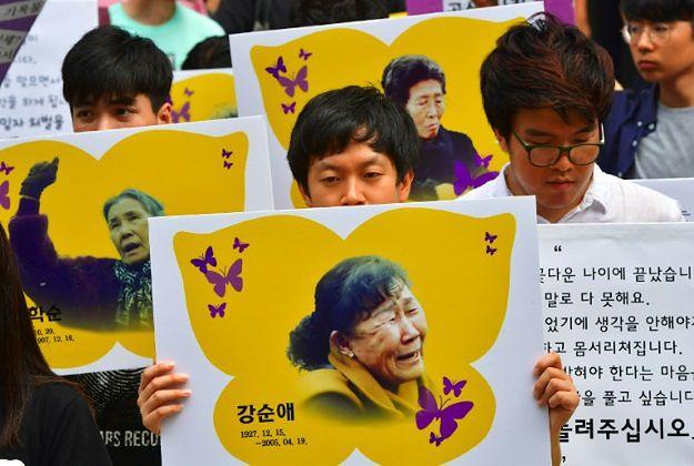 """Protestujący w Korei Południowej trzymają portrety dawnych """"kobiet do towarzystwa""""."""