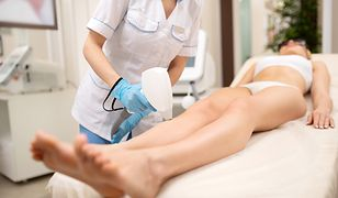 Depilation for woman. Close up of depilatory master making laser depilation for young woman