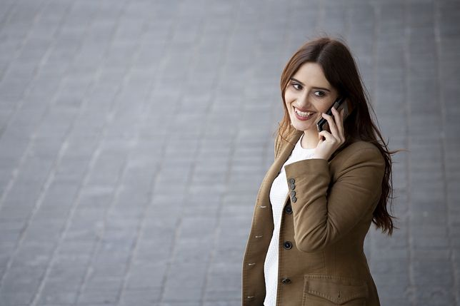 Young professional woman using a mobile phone and smiling photographed from a high angle with copy space