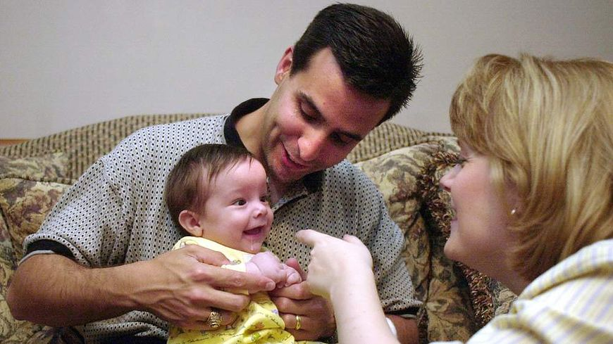 Dziecko ze zdjęcie ''Hand of Hope'' z rodzicami [http://specials.myajc.com]