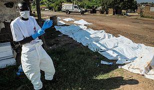 Pracownik Czerwonego Krzyża przy ciałch ofiar lipcowych walk w Dżubie
