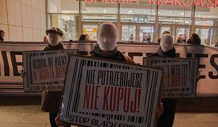 """Protest aktywistów Greenpeace Polska przed Black Friday pod hasłem """"Nie potrzebujesz - nie kupuj""""."""