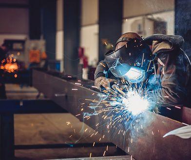 Industrial Welder With Torch and Protective Helmet in big hall welding metal profiles