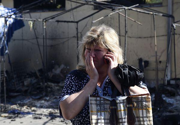 Kobieta płacze przed swoim zniszczonym sklepem w Doniecku