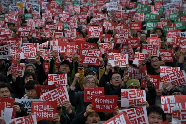 Demonstranci z hasłami nawołującymi do odejścia Park Geun-hye