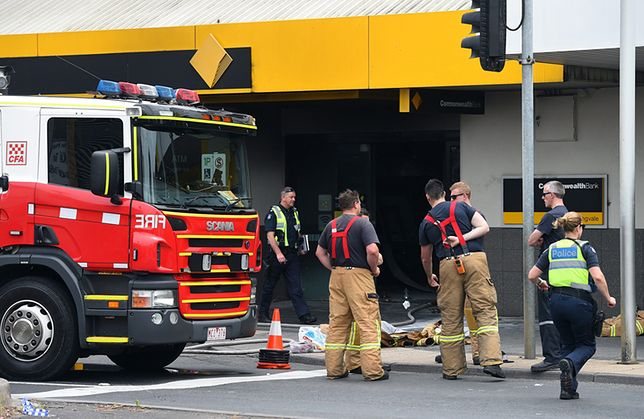 Strażacy przed spalonym oddziałem banku.