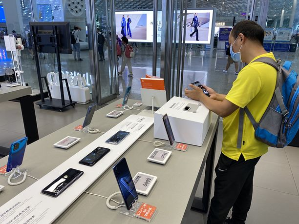 SHENZHEN - AUGUST 14: A man looks at Xiaomi smartphones at a Xiaomi experience store on August 14, 2020 in Shenzhen, Guangdong Province of China. (Photo by VCG/VCG via Getty Images)