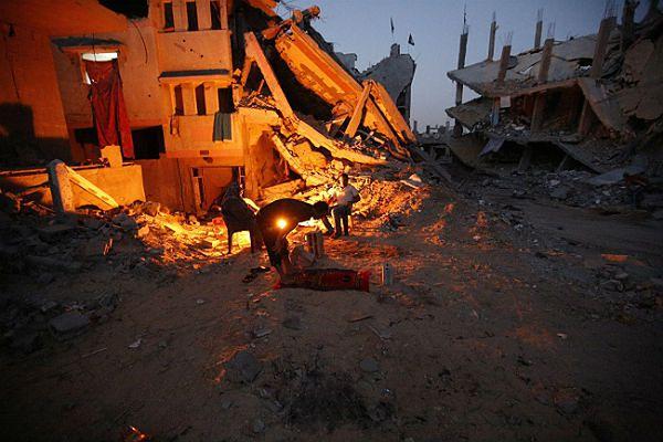 Palestyńska rodzina na gruzach tego, co zostało z ich domu po konflikcie