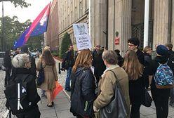 Ubrani na czarno z tęczowymi flagami. Warszawiacy zapalają znicze dla 14-letniego Kacpra przed MEN