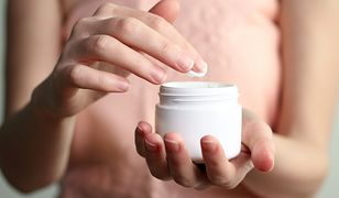 Woman dipping finger into moisturizer cream on white isolated background