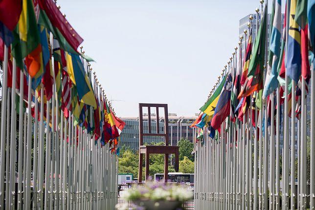 Flagi państwowe i krzesło ze złamaną nogą znajdują się na placu przed Pałacem Narodów w Genewie