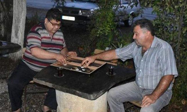 Klienci kawiarni przy zabytkowym stoliku chętnie grali w gry planszowe, takie jak popularny w Turcji tryktrak