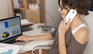 Kobieta w biurze trzyma telefon przy uchu