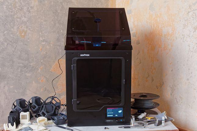 Zortrax M200 Plus w czasie pracy, z pokrywą, narzędziami i kilkoma wydrukami