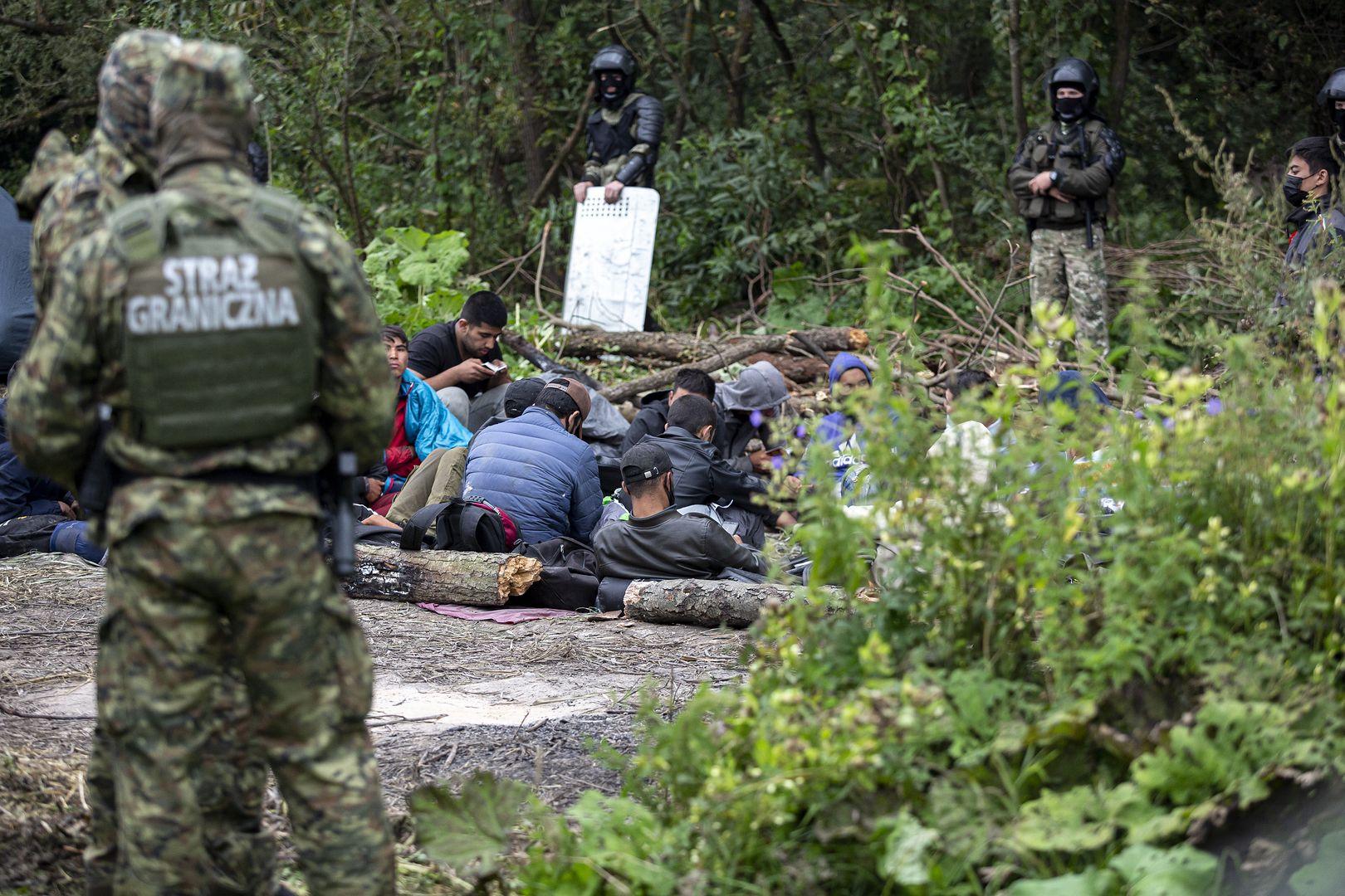 Uchodźcy między szpalerami polskiej i białoruskiej straży granicznej